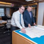 LOOKING AHEAD: David L. DeQuattro, right, managing principal of Providence-based RGB Architects, looks at building plans with Martin Holland, job captain. DeQuattro anticipates an increase in construction business in the Ocean State in 2018. / PBN PHOTO/MICHAEL SALERNO