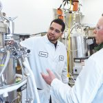 PREPARING FOR SUCCESS: Amgen Rhode Island senior associates Devon Zayas, left, and Scott Lyons conduct a safety check prior to using a bioreactor at the company's West Greenwich facility.  / PBN PHOTO/