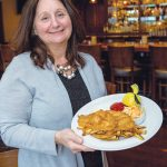 AGE-OLD FAVORITE: Joann Carlson, owner of Jo's American Bistro in ­Newport, hold's a plate of the restaurant's famous fish and chips, a 50-year-old family recipe. / PBN PHOTO/KATE WHITNEY LUCEY
