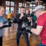 FIGHTING PARKINSON'S: Rich Gingras, center, a retired New England boxing champion, opened The Parkinson's Place gym in Pawtucket to help Parkinson's patients mitigate the effects of the disease through fitness. He works with Stuart Marshal, left, of Bristol, and Chuck Eckhardt of North Attleborough. / PBN PHOTO/MICHAEL SALERNO