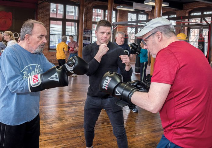FIGHTING PARKINSON'S: Rich Gingras, center, a retired New England boxing champion, opened The Parkinson's Place gym in Pawtucket to help Parkinson's patients mitigate the effects of the disease through fitness. He works with Stuart Marshal, left, of Bristol, and Chuck Eckhardt of North Attleborough. / 