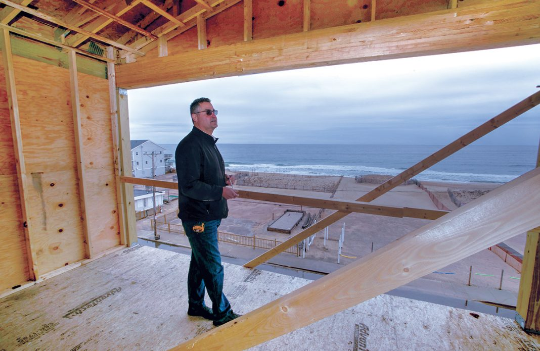 TOP VIEW: John Ballone, owner of The Hotel Maria, on the highest level of the structure under construction alongside Misquamicut Beach in Westerly designed to avoid the effects of ocean flooding by being elevated well above sea level. The Atlantic Ocean can be seen in the background. / PBN PHOTO/BRIAN MCDONALD