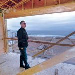 TOP VIEW: John Ballone, owner of The Hotel Maria, on the highest level of the structure under construction alongside Misquamicut Beach in Westerly designed to avoid the effects of ocean flooding by being elevated well above sea level. The Atlantic Ocean can be seen in the background. / PBN PHOTO/