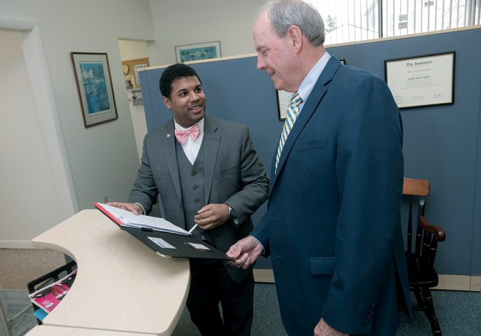 PARTNERS: Shove Insurance in Pawtucket is one of the oldest insurance companies in Rhode Island. Co-owner William J. Hunt, right, speaks with Bruce Messier, sales executive at Butler & Messier, which partners with Shove. / PBN PHOTO/MICHAEL SALERNO
