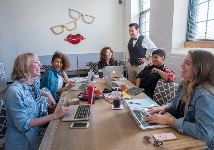 BUILDING BRANDS: David Gomez, standing, co-owner of the Red DWG Library co-working space in Pawtucket, talks with some of the users of the space. From left, seated, are: Natalie O'Sullivan, comedian; The Branding Edit co-founders: Olivia Rodrigues, Patsy Culp and Brittany Taylor; and Ashley Holmes, creative collaborator and stylist. / PBN FILE PHOTO/MICHAEL SALERNO