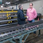 CONCERNED: Dave Waldeck, left, fabrication supervisor at VIBCO Vibrators in Richmond, speaks with CEO Karl Wadensten. VIBCO uses aluminum and steel in about 75 percent of its products and is scrambling to find enough supply and to find an agreeable price for future shipments. / PBN PHOTO/MICHAEL SALERNO