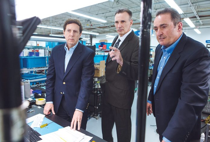 SUPPLY AND COMMAND: From left, AstroNova CEO Gregory Woods, Purchasing Manager James McGovern and Vice President of Instrument Manufacturing Stephen Petrarca review the company's new vendor-owned/managed inventory system. / PBN PHOTO/RUPERT WHITELEY