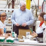 CLEAN TEAM: President and CEO Stuart Benton works on the packing floor with Bradford employees. / PBN PHOTO/RUPERT WHITELEY