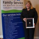 FAMILY SERVICE OF RHODE ISLAND CEO Margaret Holland McDuff stands with the Mutual of America Community Partnership Award. / COURTESY FAMILY SERVICES OF RHODE ISLAND