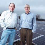 GREEN TEAM: National Marker CEO Michael Black, left, and General Manager Patrick Madigan show off the company's solar array outside its North Smithfield facility. / PBN PHOTO/RUPERT WHITELEY