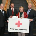 DUARTE D. SILVA, left, president and CEO of SouthCoast Federal Credit Union; Keith A. Hovan, center left, president and CEO of Southcoast Health; and Jason Mabry, right, CEO of Optimum Healthcare IT, present a check for $10,000 to Hilary V. Greene, executive director of the American Red Cross of the Cape, Islands and Southeast Massachusetts Chapter, at St. Luke's Hospital in New Bedford. / COURTESY SOUTHCOAST HEALTH