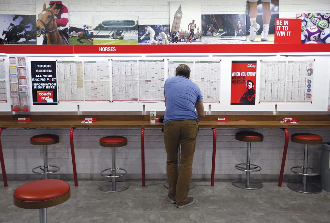 TAKING A GAMBLE: A customer reads information inside a betting shop operated by Ladbrokes Coral Group Plc., in London, in July 2015. Gov. Gina M. Raimondo is among the state leaders who would like to see Rhode Island legalize sports betting. The U.S. Supreme Court is expected to rule on a case this summer that could pave the way for that. / BLOOMBERG NEWS PHOTO/Chris Ratcliffe