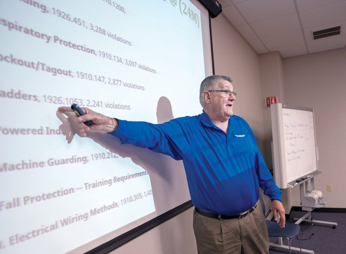 STANDING OUT: Gerry Marzilli, safety and training coordinator at Toray Plastics (America), gives a training session focusing on Occupational Safety and Health Administration safety notes from the previous year. / PBN PHOTO/MICHAEL SALERNO