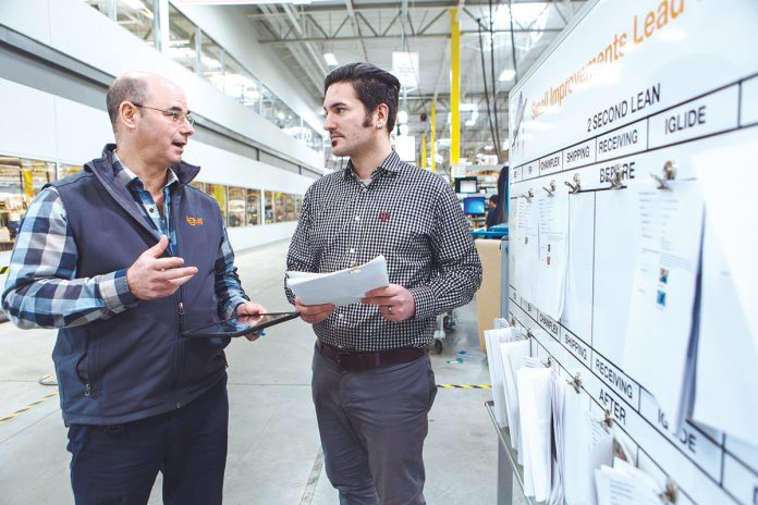 SAFETY THIRST: From left, ­Gerry Fournier, operations manager, and Mathiew Medeiros, digital marketing specialist, discuss safety tips submitted via the igus iPad safety app. / PBN PHOTO/RUPERT WHITELEY