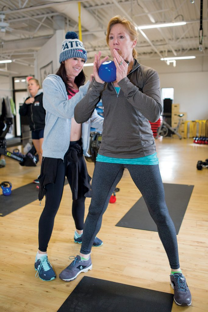 HELPING HAND: Kathy Martin, owner of Elevate Fitness in Newport, assists Tracy Mallinson of Middletown as she works out with the kettle bell during boot camp. / PBN PHOTO/KATE WHITNEY LUCEY