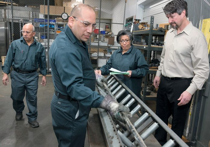 STERLING STAFF: Chad Cimini, right, president of Cimini & Associates, with employees at the manufacturer's facility in Westerly, as they work with sterling silver tubing. From left, Maldonado Ruben, background, mill operator; Neptaly Duque, mill operator; Betty Nunez, mill operator; and Cimini.