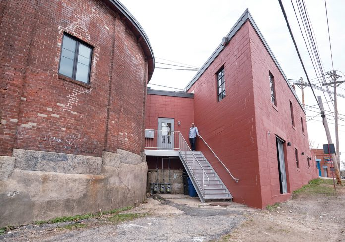 NECESSARY STEPS: On the building's exterior, new stairs and a new entrance leading into the building were constructed in an alley in between the triangular building and the rotunda that was once fenced off. / PBN PHOTO/MICHAEL SALERNO