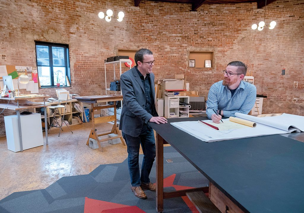 PLANNING: From left, Jay Futrell, project architect, and Eric Army, architect, have a conversation while reviewing plans for a project at Studio MEJA's rotunda office. / PBN PHOTO/MICHAEL SALERNO