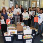 BANK RHODE ISLAND staff, volunteers and representatives from Books Are Wings with the more than 3,200 children's books collected during the bank's eighth annual book drive. Held throughout March in recognition of national reading awareness month, the effort has now generated more than 17,500 books since its inception in 2011. / COURTESY BANKRI
