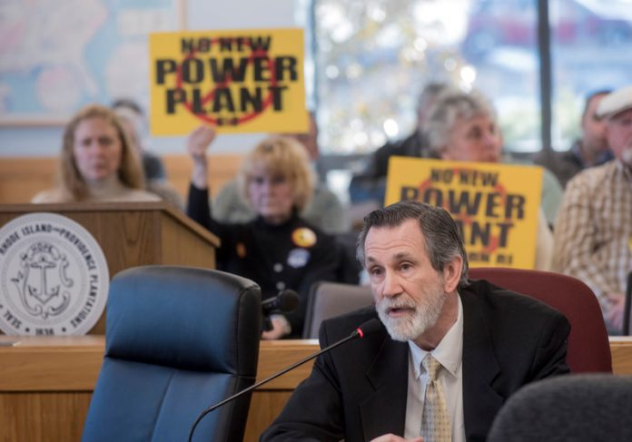 BURRILLVILLE attorney Michael McElroy speaking to the R.I. Energy Facility Siting Board in 2017 with a group opposing the proposed power plant in the background. PBN FILE PHOTO/MICHAEL SALERNO