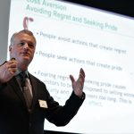 JOHN NOFSINGER, professor of finance at the University of Alaska Anchorage, speaks about the psychology of investing and how biological traits are informing investment behavior at the recent Bryant University Financial Services Forum. / COURTESY BRYANT UNIVERSITY