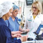 STEADY HAND: Barbara Riley, right, chief nursing officer, Rhode Island Hospital and Hasbro Children's Hospital, speaks with registered nurses Wendy Rocha, left, and Sarah Smith at Hasbro. / PBN PHOTO/RUPERT WHITELEY