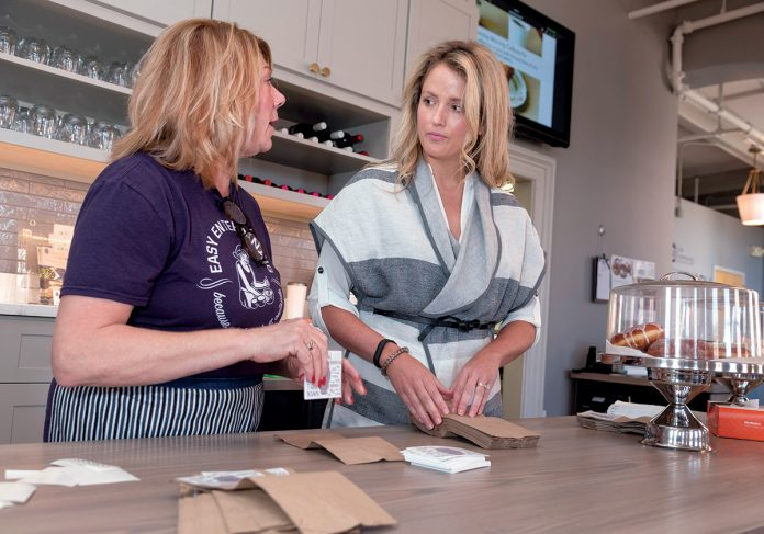 HELPING HAND: Tammy Delfino, left, server, and Kaitlyn Roberts, owner of Easy Entertaining in Providence, prepare for an event. / PBN PHOTO/MICHAEL SALERNO