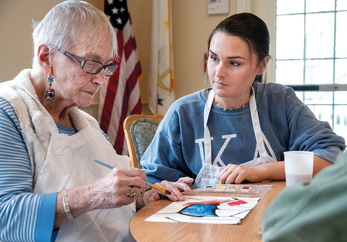 "ABSTRACT ART: University of Rhode Island students have been working with clients of Cornerstone Adult Services in Warwick this semester on an art project called ""Opening Minds through Art."" Molly Richards, right, of Cape Cod, Mass., a URI sophomore in human development and family studies, with a minor in psychology, works with Margaret Pleau of Warwick on a watercolor painting. / PBN PHOTO/