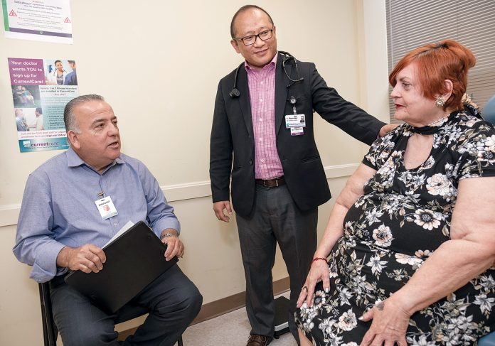 SEASONED INTERPRETER: Jose Cruz, left, is a medically certified interpreter who has worked for Pinpoint Translation Services in Providence for more than a decade. Cruz speaks with Elba Morales, right, of Providence, a Spanish-speaking resident of PACE Organization of Rhode Island, as Dr. Tsewang Gyurmey looks on. / PBN PHOTO/MICHAEL SALERNO