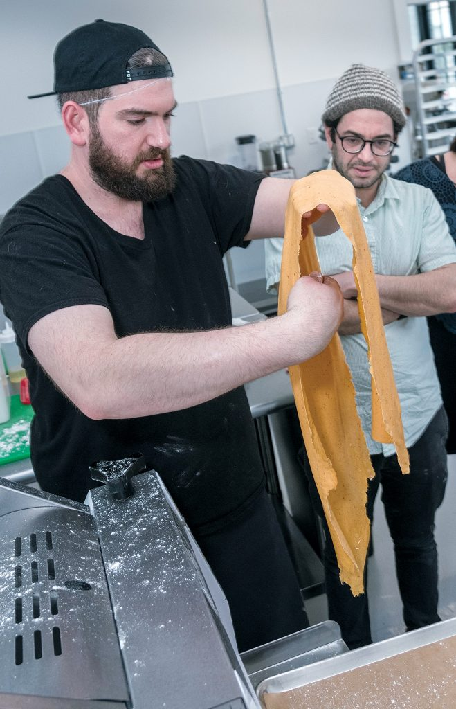 SHARED WORKSPACE: Avi Mallinger, right, general manager of Pilotworks Providence, a shared commercial kitchen space available for use by local small food-production companies, discusses how to use the dough sheeter with Andrew Kupke, chef and co-owner of Brown Paper Bounty. / PBN PHOTO/MICHAEL SALERNO