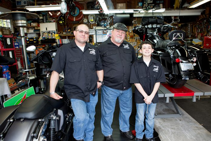 "HAVING FUN: James ""Big Jim"" Annis, right, and James ""Jimmy"" Annis, left, with Robert James Annis, at East Bay Custom Cycles in Bristol, a motorcycle customize and repair shop, which Big Jim and Jimmy opened together last May. / PBN PHOTO/KATE WHITNEY LUCEY"
