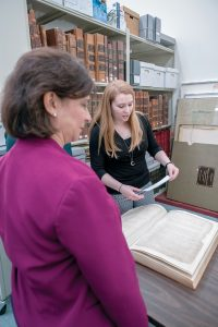 HISTORICAL DOCUMENTS: Ashley Selima, right, state archivist and public records administrator, discusses the history of the documents with Secretary of State Nellie M. Gorbea at the Rhode Island state archives in Providence. / PBN PHOTO/MICHAEL SALERNO