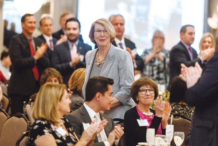 AT THE TOP OF HER GAME: BankNewport President and CEO Sandra J. Pattie heads to the podium at the 2018 PBN Business Women Awards luncheon to accept her Career Achievement award.  / PBN PHOTO/