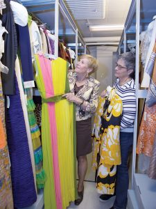 Trudy Coxe, Preservation Society of Newport County CEO and executive director, with Andrea Carneiro, PSNC spokesperson, in the textiles collection storage room at the PSNC headquarters in Newport, where they have clothing from Colonial times to the present. / PBN PHOTO/KATE WHITNEY LUCEY