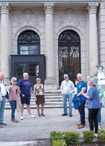 Trudy Coxe, Preservation Society of Newport County CEO and executive director, , center, joins a group outside The Elms to listen to guide Nancy Christy giving a tour. / PBN PHOTO/KATE WHITNEY LUCEY