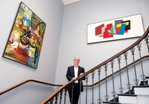 """MUSEUM EXHIBITS: Rhode Island School of Design Museum Director John W. Smith with museum exhibits, from left, """"Homage to Matisse"""" by Grace Hartigan and """"Still Life with Bottle and Two Glasses"""" by Patrick Caulfield. / PBN PHOTO/MICHAEL SALERNO"""