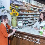 MODERN CLASSIC: Pharmacist Christina Procaccianti, right, operates a modern version of a classic American drugstore. Green Line Apothecary is on Main Street in South Kingstown. Above, she talks with Laura Taylor of Exeter at the drop-off counter. / PBN FILE PHOTO/­MICHAEL SALERNO