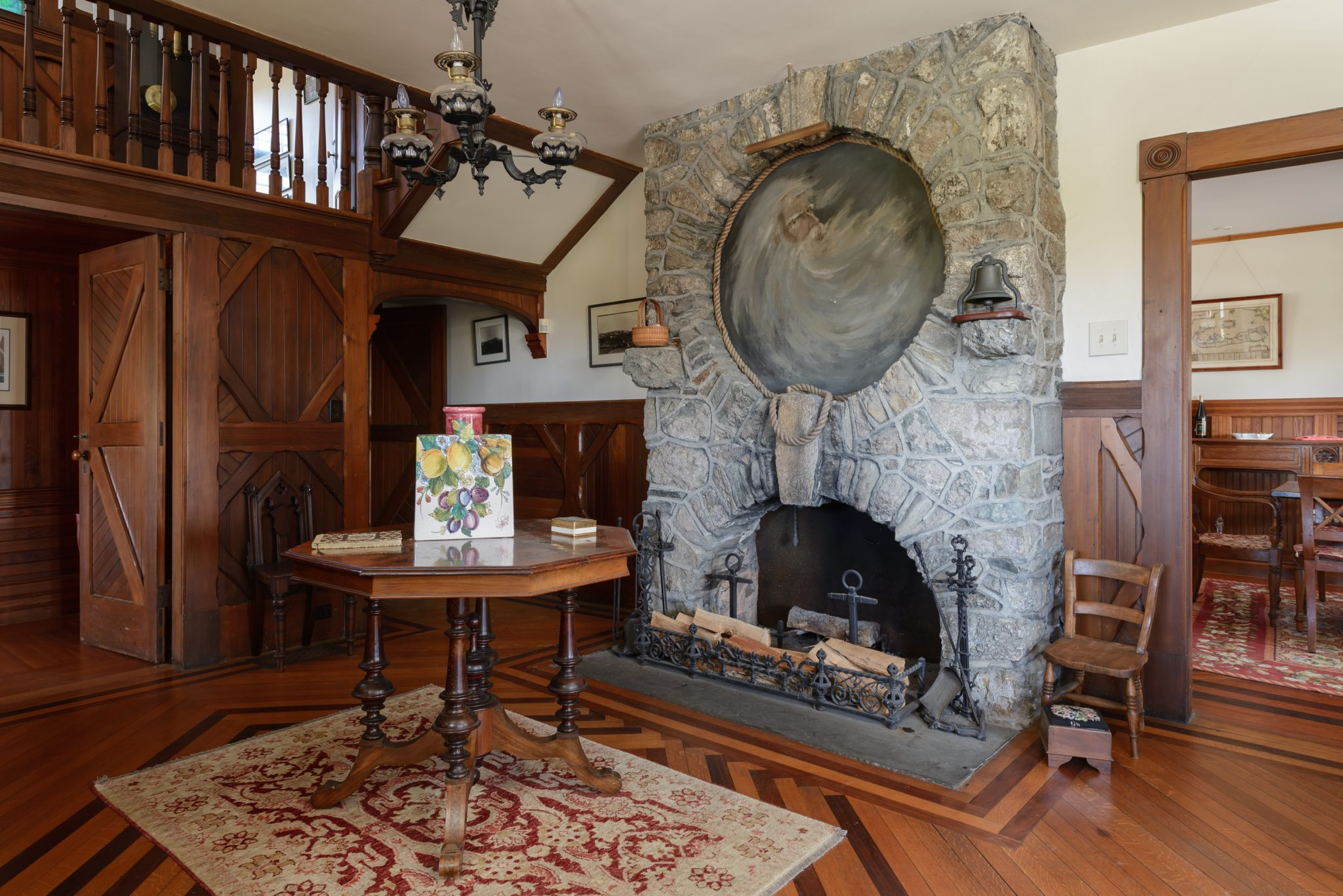 """A PORTRAIT OF """"Old North Wind"""" by landscape artist William Trost Richards hangs above this original stone fireplace. / COURTESY CONCIERGE AUCTIONS"""