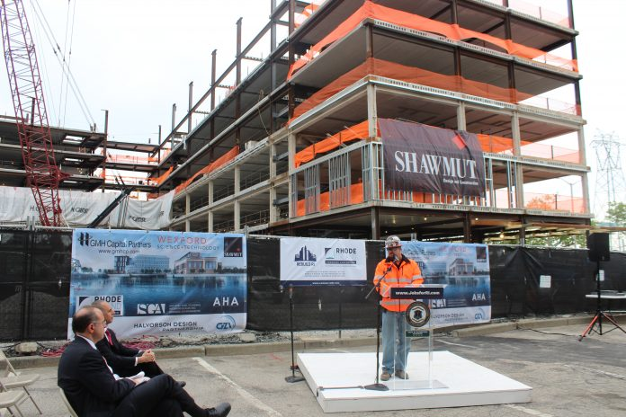 JAMES WOODWARD, superintendent at Shawmut Design and Construction, speaks during the topping off ceremony for the River House apartments project, in which the final steel beam is placed atop the structure. Seated are Commerce Secretary Stefan Pryor, foreground, and Providence Mayor Jorge O. Elorza. / COURTESY SHAWMUT
