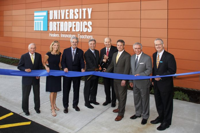 UNIVERSITY ORTHOPEDICS recently opened a new location in East Providence. From left: Edward Burman Jr., president of EW Burman; Kathy Snelgrove, chief operating officer of University Orthopedics; Michael Integlia, president of Michael Integlia & Co.; Dr. Mark Palumbo, University Orthopedics; Dr. Edward Akelman, president of University Orthopedics; Weber Shill, CEO of University Orthopedics; Mehdi Khosrovani, president of NEMD Architects; East Providence Mayor James Briden. / COURTESY SHANE PHOTOGRAPHY
