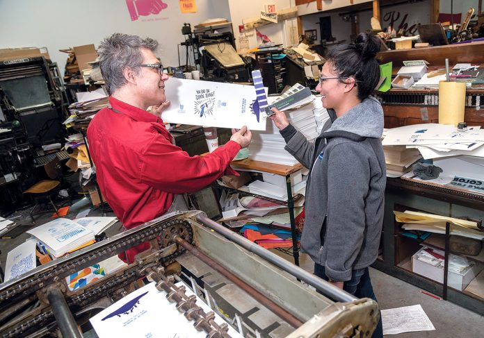 LASTING LETTERPRESS: Dan Wood, owner and founder of the Dan Wood Rhode Island letterpress print shop, works with Lois Harada, shop manager, on the Polyman 50 automatic-fed cylinder letterpress at the shop's headquarters in Providence. / PBN PHOTO/MICHAEL SALERNO