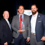 STEADFAST SUPPorT: Michael Baker, CEO of Pet Food Experts, accepts an award on behalf of his family from the YMCA of Greater Providence for their longtime service to the Newman YMCA of Seekonk during a Y Heroes Luncheon at the R.I. Convention Center April 12. From left, Greater Providence of YMCA CEO Steven O'Donnell, Baker and New England Patriots fullback James Develin. / COURTESY PET FOOD EXPERTS