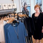 POPULAR DESIGNS: Robin Barrett Wilson, CEO and founder of robin b., a 3-year-old women's fashion design and boutique in Cranston, wears one of her designs, a black sleeveless sheath dress underneath a cardigan sweater, both made in New York. The outfit on the rack next to her has a Lola & Sophie top and Parkes Smith jeans. / PBN PHOTO/MICHAEL SALERNO