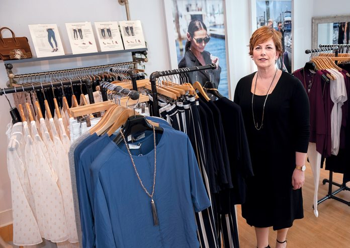 POPULAR DESIGNS: Robin Barrett Wilson, CEO and founder of robin b., a 3-year-old women's fashion design and boutique in Cranston, wears one of her designs, a black sleeveless sheath dress underneath a cardigan sweater, both made in New York. The outfit on the rack next to her has a Lola & Sophie top and Parkes Smith jeans.
