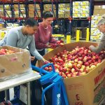 HELPING HANDS: Rhode Island Foundation employees help sort food at the Rhode Island Community Food Bank in October 2017.