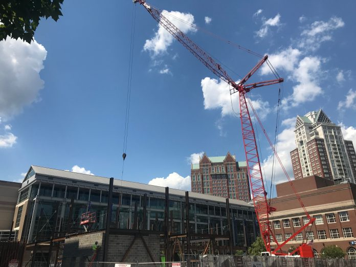 A 240-FOOT CRANE installs structural steel beams at the Residence Inn hotel site in Providence this week, marking the beginning of vertical construction, which is expected to continue through the summer. / PBN FILE PHOTO/CHRIS BERGENHEIM