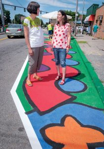 WALKING TOUR: Marta V. Martinez, left, executive director of Rhode Island Latino Arts and host of the Broad Street neighborhood walking tour, stops along the route with Tamara Diaz, the artist who painted the mural they are standing on. / PBN PHOTO/MICHAEL SALERNO