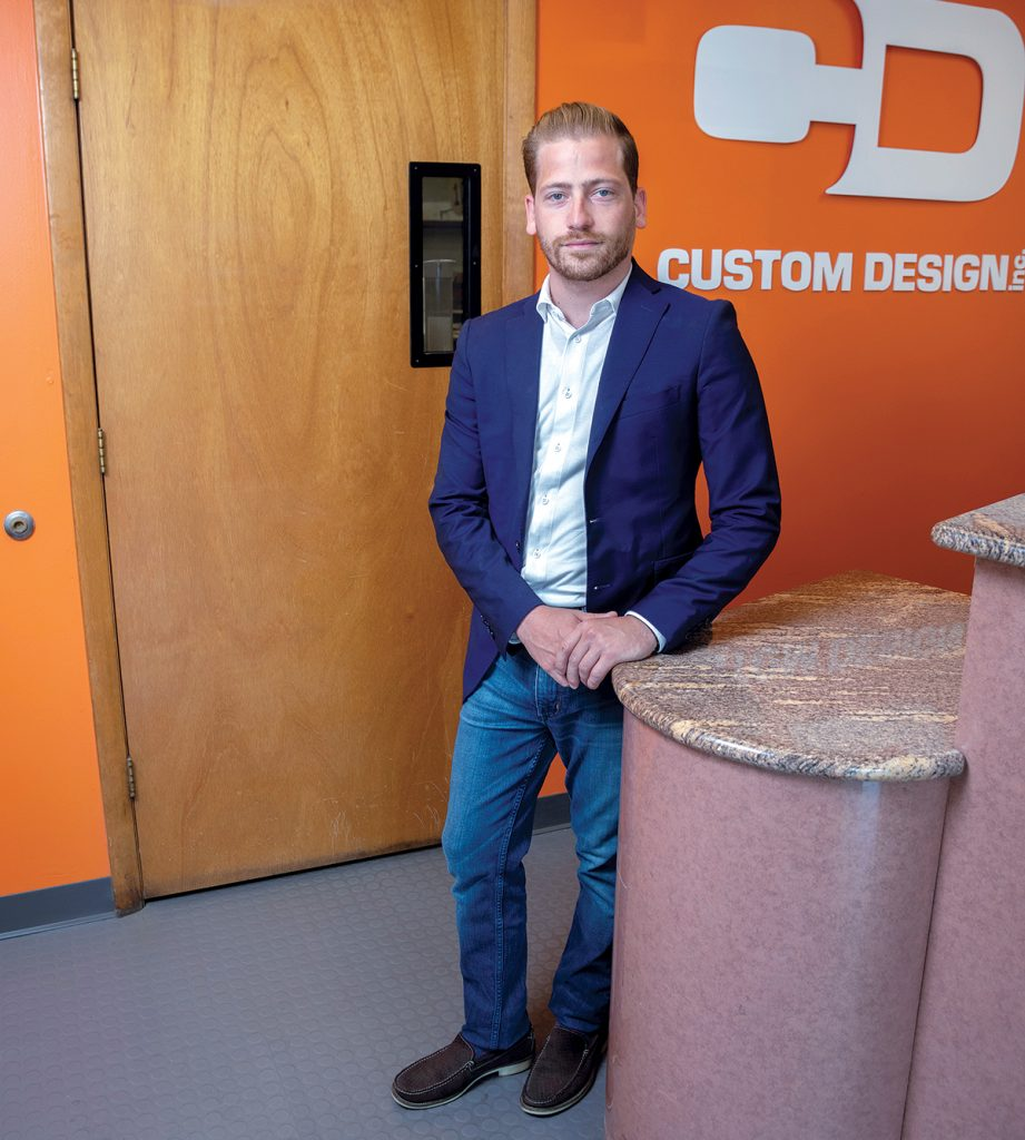 Custom Design Inc. has been making merchandising displays and store fixtures for retailers since 1976. Adam Dias took over from his father, Raul Jr., recently and looks to the future through the lens of past success. / PBN PHOTO/MICHAEL SALERNO