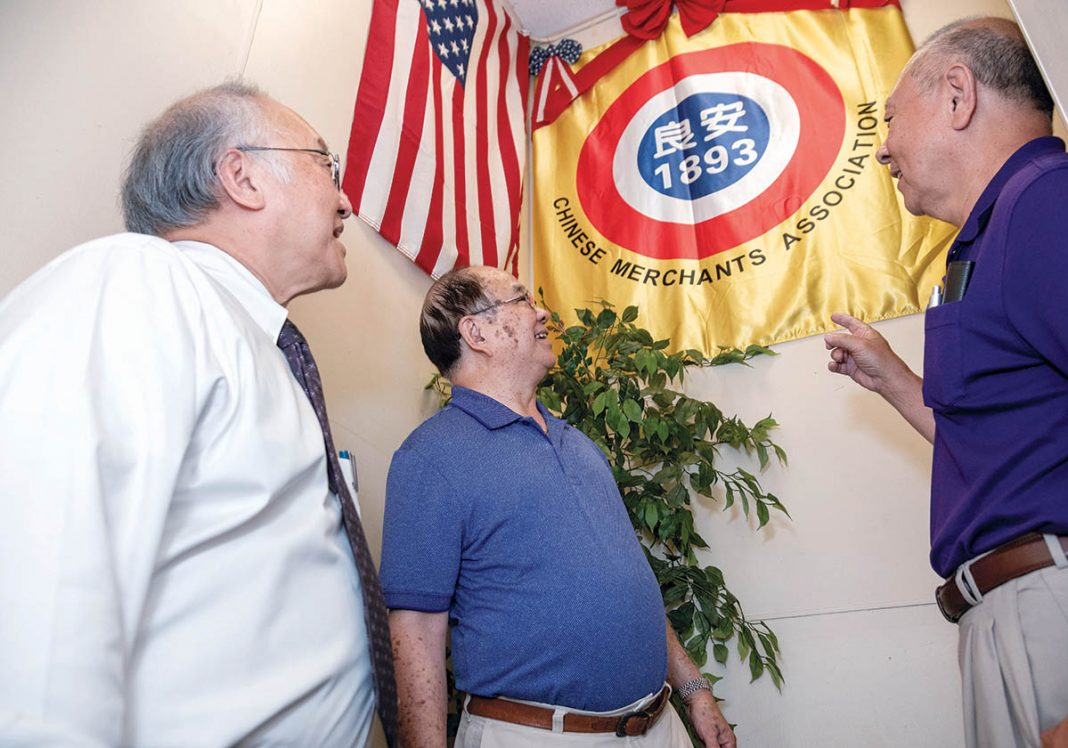 FAMILY CONNECTION: Charles Chin, left, president of the Rhode Island chapter of the On Leong Chinese Merchants Association in Cranston, Peter Kwong, center, and Edward Moy look at an association flag. Moy's grandfather was a past president of the association.
