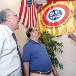 FAMILY CONNECTION: Charles Chin, left, president of the Rhode Island chapter of the On Leong Chinese Merchants Association in Cranston, Peter Kwong, center, and Edward Moy look at an association flag. Moy's grandfather was a past president of the association. / PBN PHOTO/MICHAEL SALERNO